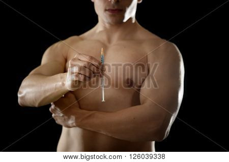 young body building sportsman using steroids for increasing sport and athletic performance holding syringe isolated on back background in sport cheat doping and illegal use of hormones