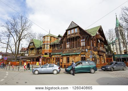 ZAKOPANE POLAND - MARCH 06 2016: View towards wooden building which until 1898 was the biggest hotel in Zakopane nowadays it houses a restaurant called Gazdowo-Kuznia