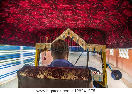 VARKALA, INDIA - OCTOBER 18, 2015: Unidentified driver of auto rickshaw in Varkala. Auto rickshaws are used in cities and towns for short distances and they provide cheap and efficient transportation.