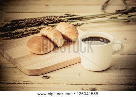 Coffee Cup And Bread On Wooden Floor
