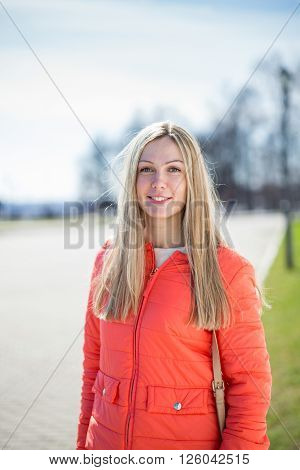 Outdoors portrait of beautiful young  woman looking at camera.