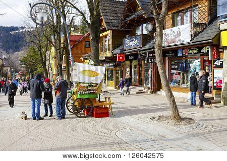 ZAKOPANE POLAND - MARCH 06 2016: Unidentified tourists are buying Oscypek cheese at Krupowki street since February 02 2007 Oscypek is Polish regional product protected by EU law