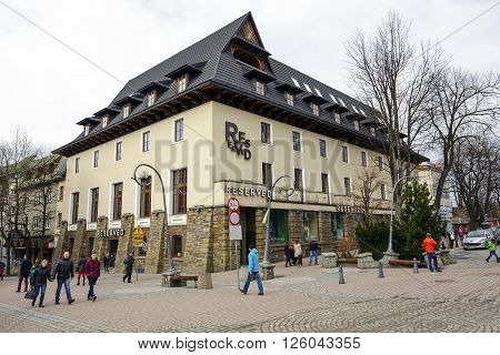 ZAKOPANE POLAND - MARCH 06 2016: Brick Building of Giewont Hotel existing since 1955 built according to the design of Juliusz Zorawski the largest clothing store brand Reserved from June 29 2013