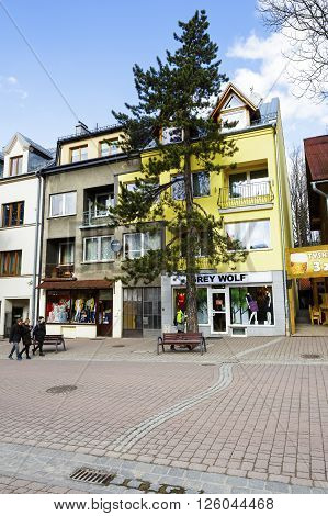 ZAKOPANE POLAND - MARCH 09 2016: Brick townhouse probably from the early twentieth century located at the lower part of Krupowki. On the ground floor of this building there are two shops
