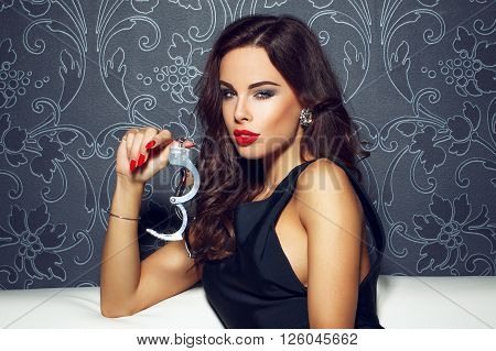 Sexy woman with red lips showing handcuffs at vintage wall. Jessica Rabbit retro style bdsm.