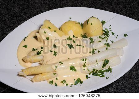 cooked white asparagus with potatoes and parslay