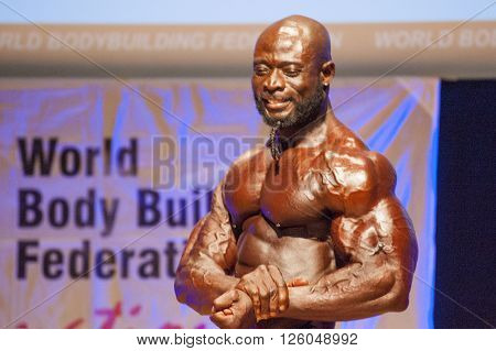 MAASTRICHT THE NETHERLANDS - OCTOBER 25 2015: Male bodybuilder Elias Bogane flexes his muscles and shows his best physique in a chest pose on stage at the World Grandprix Bodybuilding and Fitness of the WBBF-WFF