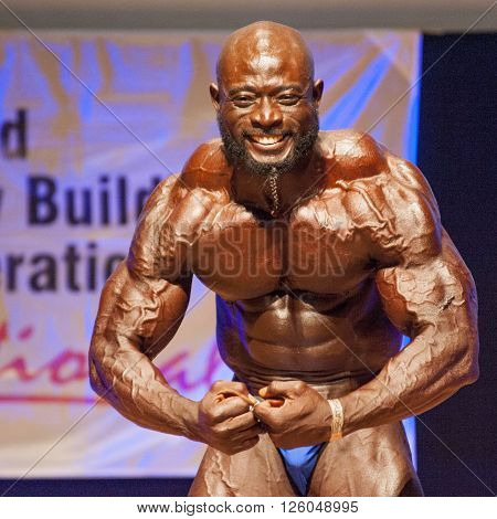MAASTRICHT THE NETHERLANDS - OCTOBER 25 2015: Male bodybuilder Elias Bogane flexes his muscles and shows his best physique in a most muscular pose on stage at the World Grandprix Bodybuilding and Fitness of the WBBF-WFF