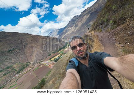 Fellow traveler taking selfie while visiting Inca site of Pisac Sacred Valley major travel destination in Cusco region Peru. Expansive view.