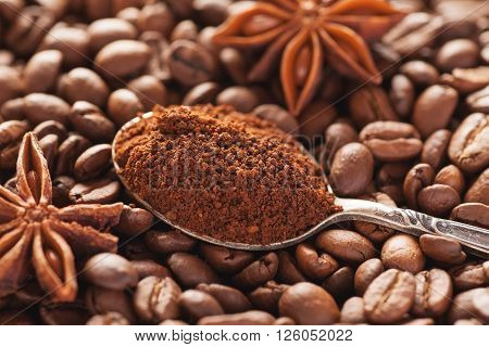 Grounded coffee in silver spoon above coffee beans star anise closeup shot