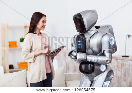Modern world. Pleasant beautiful delighted girl using tablet and expressing gladness while standing with robot