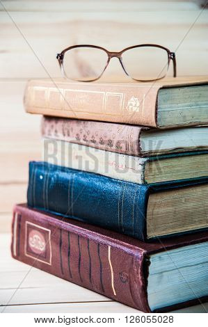 Stack of books with glasses on wooden desk on wooden background