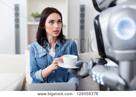 Thanks a lot. Pleasant attractive girl sitting on the sofa and  using laptop while getting  cup of coffee from the robot