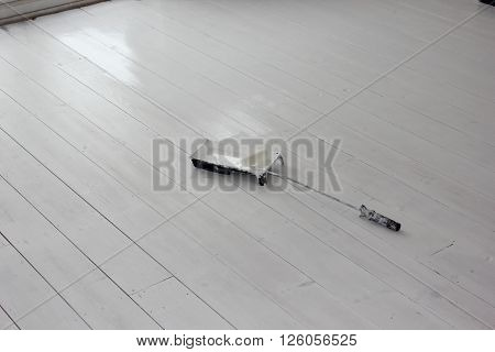 A roller and paint tray on newly painted white floorboards