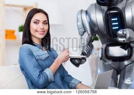 Nice house keeper. Cheerful delighted attractive girl sitting on the couch and using laptop while  getting cup of coffee from her robot