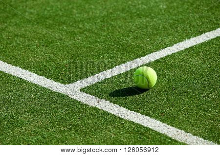 tennis ball on green tennis grass court
