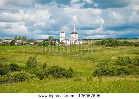 Russian summer landscape with a field and the white church
