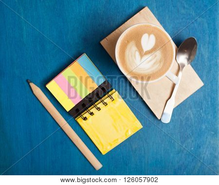Top view close-up of cup of coffee with spoon, writing-pad, pencil on desk