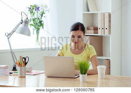 Beautiful young woman is typing on a laptop in her office. She is sitting at the desk and smiling