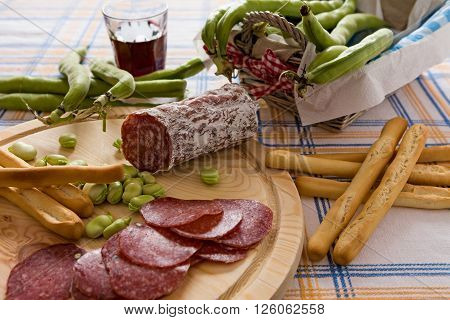 Italian salami broad bean and bread sticks over a chopping board