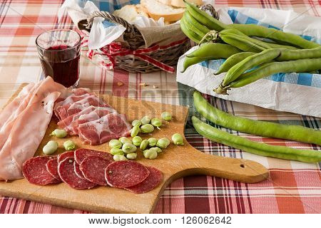 Trattoria table with cold meats broad bean and red wine