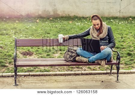 Young female student sitting on park bench, drinking a coffee and working with her laptop