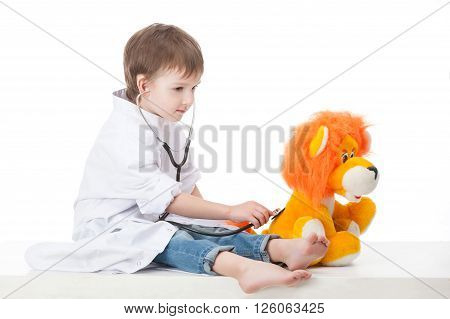 Baby boy in a white robe doctor makes an injection syringe toy lion cub . Isolated on white  background