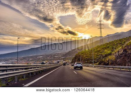 TENERIFE, SPAIN - DECEMBER 2015: Auto highway with small traffic during sunset on Tenerife island, Spain