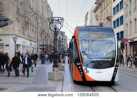 GENEVA SWITZERLAND - NOVEMBER 28: Tram at the Rue du Rhone with people on November 28 2015 in Geneva Switzerland.
