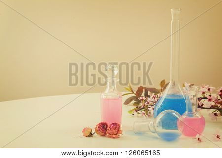 Dry flowers, vials and bottles of tincture or oil, aromatherapy concept, retro toned