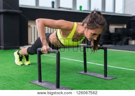 young fit woman doing horizontal push-ups with bars in gym