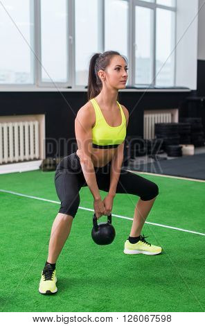 side view portrait of an athlete woman doing exercises lifting kettlebell in gym working out back, legs muscles