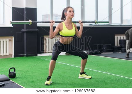 young fit woman doing squats with barbell, exercising back and legs muscles.