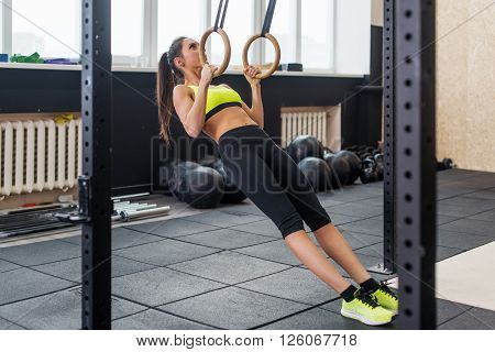 fit woman doing pull-ups with gymnastic rings in gym, young female working out biceps, triceps, abs.
