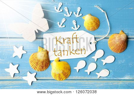Flat Lay View Of Label With German Text Kraft Tanken Means Relax. Sunny Summer Greeting Card. Butterfly, Shells And Fishes On Blue Wooden Background