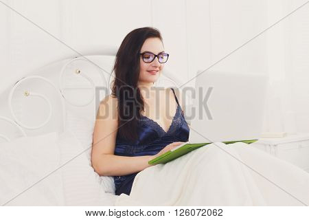 Middle aged woman with laptop in white bed. Woman in eyeglasses looks into gadget pc. Morning in bed. Beautiful woman in blue nightwear at bed surfing internet at her computer. High key. Soft tone