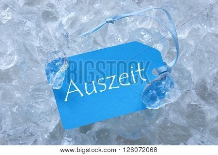 Light Blue Label With Blue Ribbon On White Transparent Curshed Ice Cubes As Background. German Text Auszeit Means Downtime For Cool Greetings.Close Up Or Macro View.