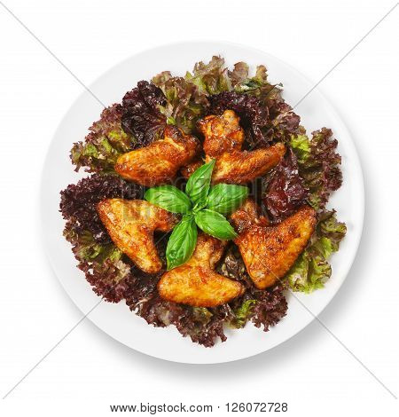 American cuisine, restaurant food -  fried roasted chicken wings on lettuce with basil at round white plate closeup isolated. Top view, flat lay