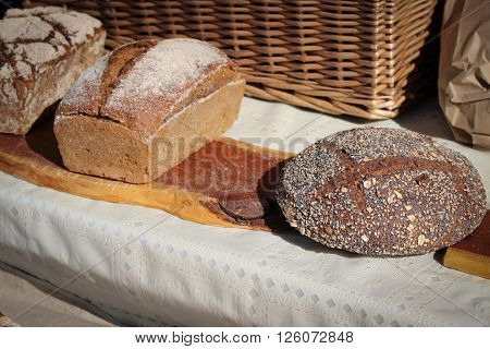 Loaves of artisan bread for sale at a farmer's market.