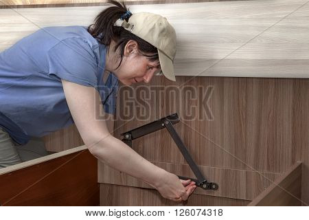Woman assembles furniture for sleeping steel hinges lifting mechanism screwed to the frame.