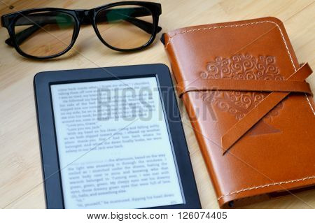 Black ereader with reading glasses and an old notebook in leather cover on wooden table