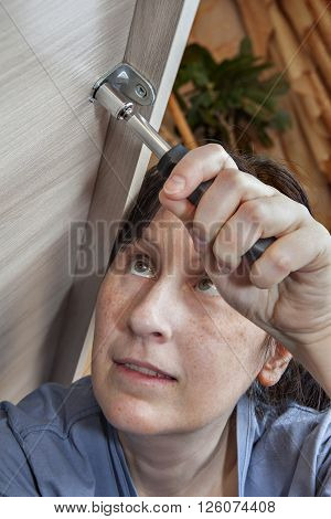 Caucasian woman tighten nut using Nut Spinner Screwdrivers close-up girl putting together self assembly furniture.