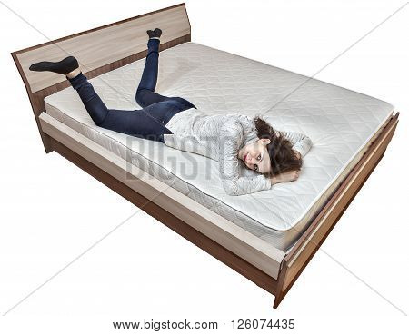 One young Caucasian girl is resting on bed innerspring mattress wooden bedstead isolated on white background.