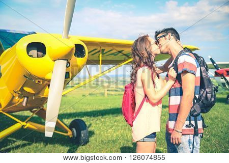 Couple kissing with a airplane in the background - Girlfriend kissing her man before he leaves for a long journey
