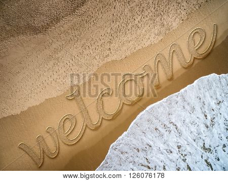 Welcome written on the beach