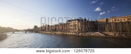 PARIS, FRANCE - MARCH 26, 2016:  View of famous Louvre Museum from the Seine River at sunset. Louvre Museum is one of the largest and most visited museums worldwide.