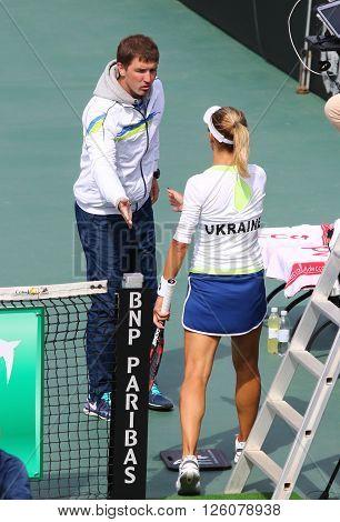 KYIV UKRAINE - APRIL 16 2016: Captain of Ukraine National Team Mikhail Filima (L) and player Lesia Tsurenko during BNP Paribas FedCup game Ukraine vs Argentina at Campa Bucha Tennis Club in Kyiv