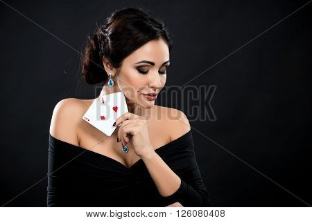 sexy woman with poker cards. Female player in a beautiful black dress