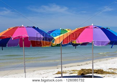 Three Colorful Beach Umbrellas with Ocean and Sky in the Background