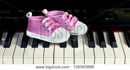 Pink baby shoes on piano key board.